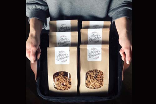 A person holding a tray of granola packages